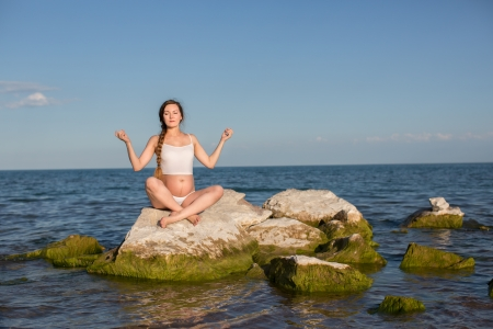 Pregnant woman  in sports bra doing exercise in relaxation on yoga pose on ocean photo