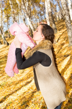 Happy young mother playing with little daughter in autumn park Stock Photo - 16142550