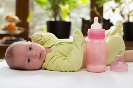 Newborn baby girl with a bottle of milk  The concept of food and parenting Stock Photo - 16142512