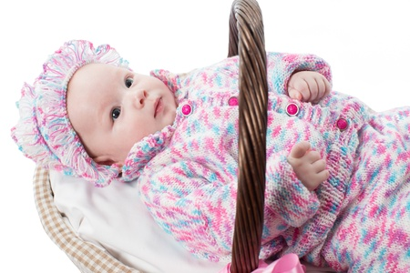 3 persons only: adorable girl child in a knitted suit in basket on white background isolated