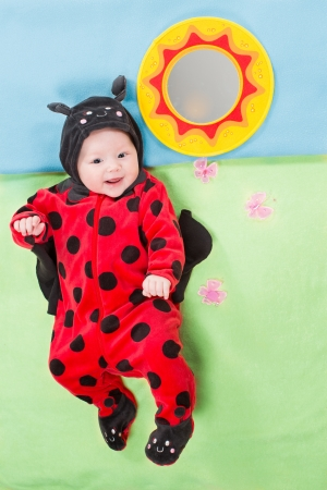 Pretty baby girl, dressed in ladybug costume on green background  The concept of childhood and holiday photo