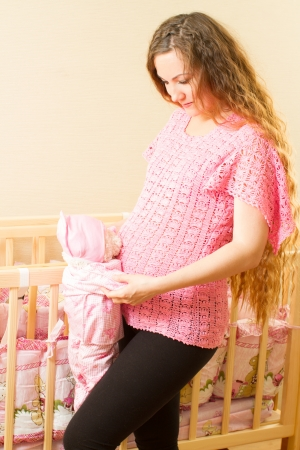 Pregnant woman with long hair and toy Teddy bear near a crib photo