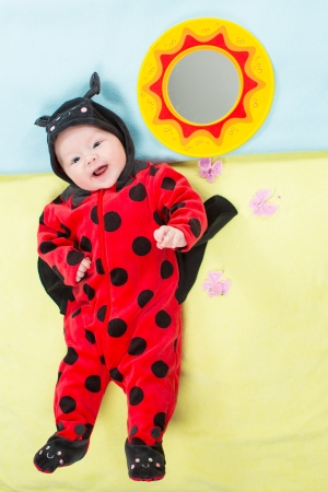 Pretty child girl, dressed in ladybug costume on green background  The concept of childhood and holiday Stock Photo - 17253962