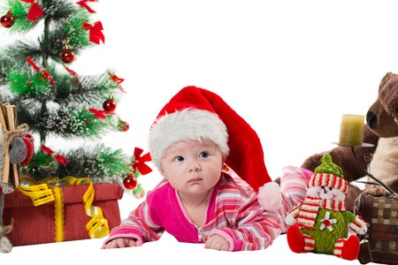 baby near christmas tree: Santa baby girl near Christmas tree and gift on isolated white background  The concept of childhood and holiday