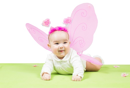 Pretty child girl, dressed in butterfly costume on green background  The concept of childhood and holiday