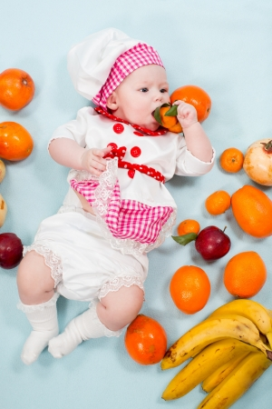 Baby girl  wearing a chef hat with fruits. Use it for a child, healthy food concept photo