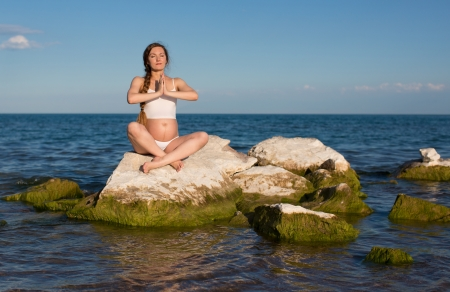 Pregnant woman in sports bra doing exercise in relaxation on yoga pose on sea photo