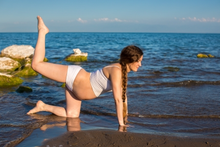Pregnant woman in sports bra doing exercise in relaxation on yoga pose on sea   The concept of health and sport photo