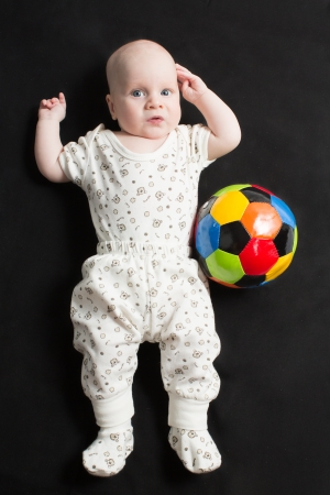 Baby boy playing with a soccer ball on black background  Babies And Children photo