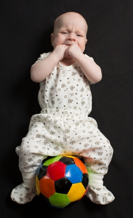 Baby boy playing with a soccer ball on black background photo