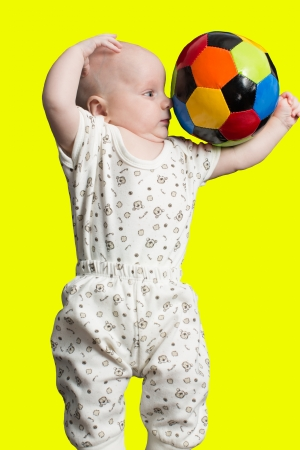 Baby boy playing with a soccer ball on color background photo