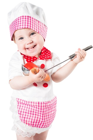 Baby girl wearing a chef hat with vegetables and pan isolated on white background.The concept of healthy food and childhood photo