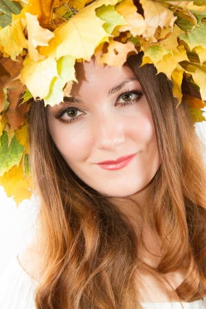 Beautiful fall woman. Portrait of girl with autumn wreath of maple leaves on head on isolated white background photo