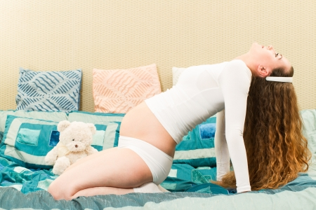 Pregnant woman with long hair in a yoga pose on sofa at home. The concept of the family and parents photo