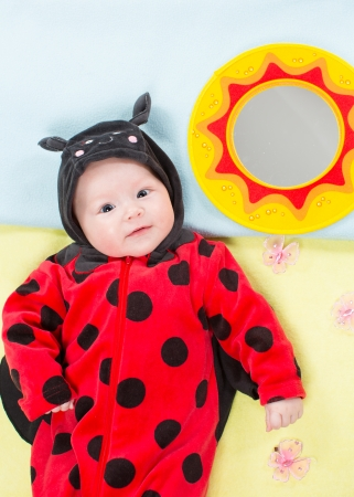 Pretty baby girl, dressed in ladybug costume on green background. The concept of childhood and holiday photo