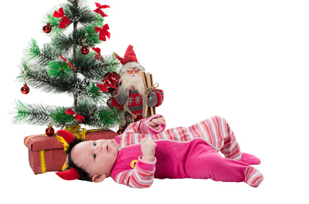 baby near christmas tree: Santa baby girl near Christmas tree and gift on isolated white The concept of childhood and holiday