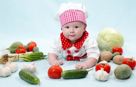 Baby cook girl wearing chef hat with fresh vegetables. Use it for a child, healthy food concept photo