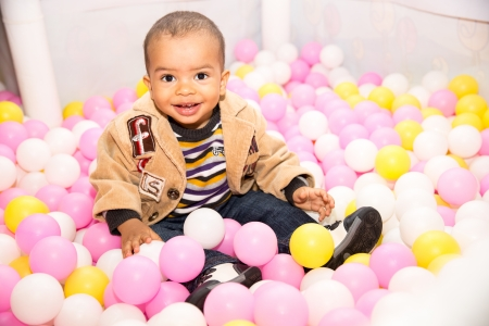 Happy black boy in colored ball on birthday on playground  The concept of childhood and holiday photo