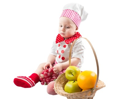Baby cook boy wearing chef hat with basket with fresh fruit  Use it for a child, healthy food concept photo