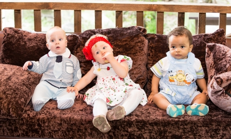 Small three children: black american, caucasian boys and russian baby girl siting up on sofa Stock Photo