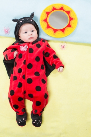 0 3 months: Pretty baby girl, dressed in ladybug costume on green background. The concept of childhood and holiday Stock Photo