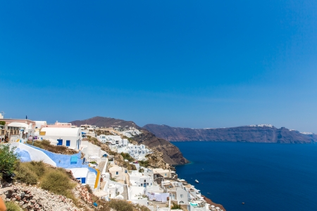 staircases: View of Fira town - Santorini island,Crete,Greece. White concrete staircases leading down to beautiful bay with clear blue sky and sea