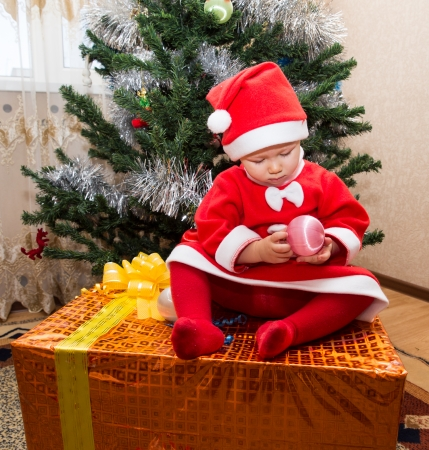 Santa baby girl  with gift box near Christmas tree at home photo