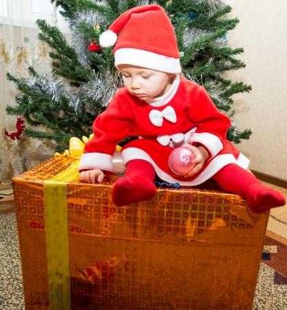 Santa baby girl with gift box near Christmas tree at home photo