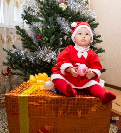 baby near christmas tree: Santa baby girl  with gift box near Christmas tree at home
