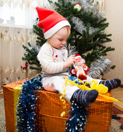 Santa baby boy  with gift box near Christmas tree at home photo