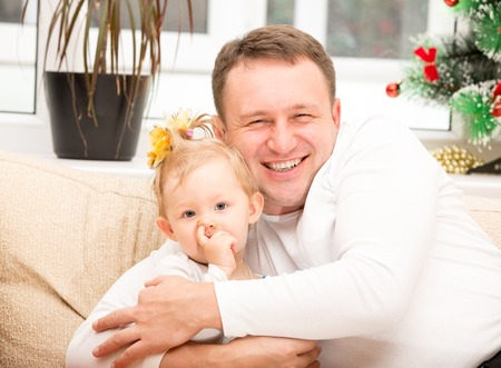 Happy father and child girl hugging and laughing on isolated white photo