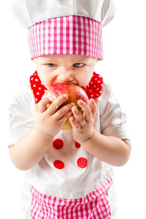 Baby cook girl wearing chef hat with fresh apple. Use it for a child, healthy food concept photo