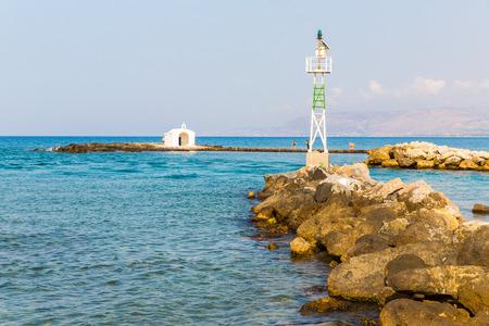 Old venetian lighthouse at harbor in Crete, Greece. Small cretan village Kavros. Travel Background photo