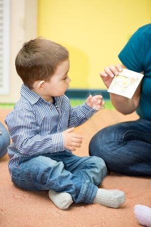 Little child boy playing in kindergarten in Montessori preschool Class.