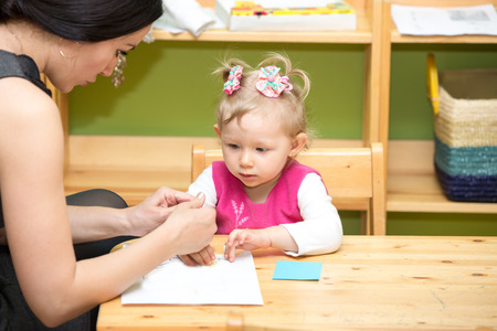 Mother and child girl drawing together with color pencils in preschool at the table in kindergarten photo