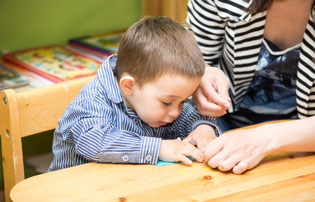 Mother and child boy drawing together with color pencils in preschool at the table in kindergarten photo
