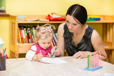 Mother and child girl playing in kindergarten in Montessori preschool Class. Imagens