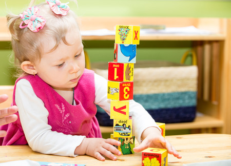 Little child girl playing with toy letter and number blocks  in kindergarten in Montessori preschool Class. Stock Photo