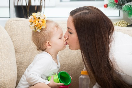 Happy mom and child girl hugging and kissing at home  The concept of cheerful childhood and family  Beautiful Mother and her baby photo
