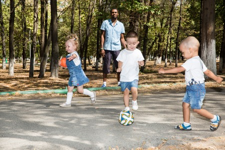 Group of happy children playing with soccer ball in park on nature at summer. Use it for baby and sport concept Stock Photo