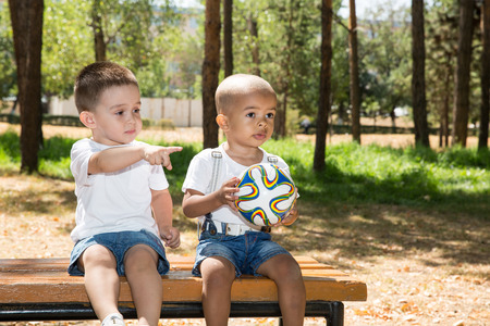 Little boys: African American and caucasian  with soccer ball in park on nature at summer. Use it for baby and sport  concept photo