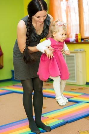 Mother and child girl playing in kindergarten in Montessori preschool Class. photo