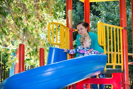 Happy adorable girl with mom on childrens slide on playground near kindergarten Montessori on summer day photo