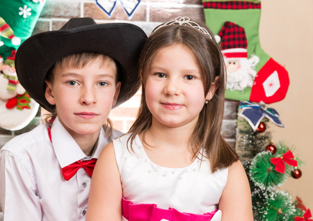 Boy gentleman and girl in ball dress by fireplace. Christmas and New Year photo