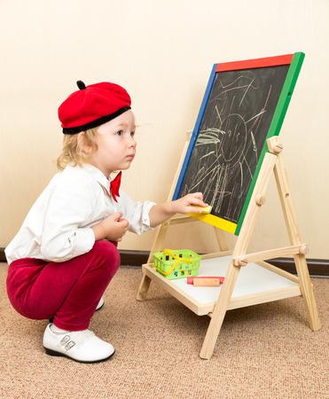 Cute child girl drawing chalk on easel in suit of artist in preschool in kindergarten photo