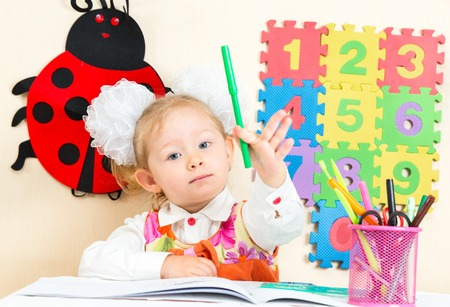 tot: Cute child girl drawing with colorful pencils in preschool at table in kindergarten Stock Photo