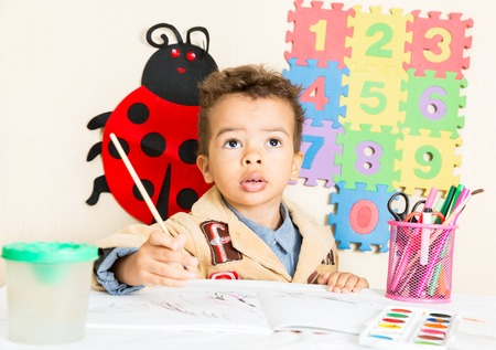 tot: African American black boy drawing with colorful pencils in preschool at table in kindergarten