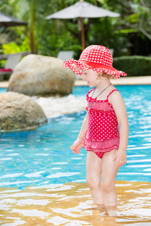 Funny little child girl near swimming pool on  tropical resort in Thailand, Phuket. Summer vacations and sport  concept