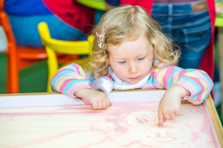 montessori: Cute child girl drawing draws developing sand in preschool at table in kindergarten by method of Montessori