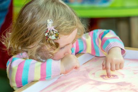 kinder: Dibujo lindo muchacha niño dibuja la arena en desarrollo en el preescolar a la mesa en el jardín de infantes por el método de Montessori Foto de archivo